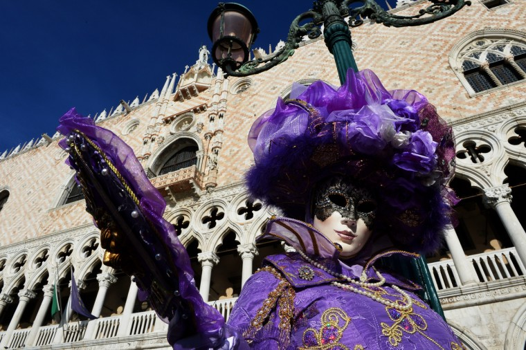 "A costumed reveller poses at St Mark's square during the carnival on February 3, 2013 in Venice. The 2013 edition of the Venice carnival is untitled "" Live in Colour"" and runs from January 26 to February 12. (Vincenzo Pinto/Getty Images)"