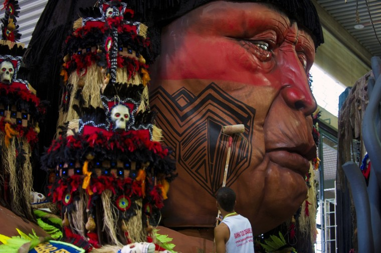 A member of Imperatriz Leopoldinense samba school paints an indigenous dummy face atop a float during preparations for the famous carnival parade at the Sambodromo, on February 4, 2013 in Rio de Janeiro. The samba schools parade will be held next February 10 and 11. (Antonio Scorza/Getty Images)