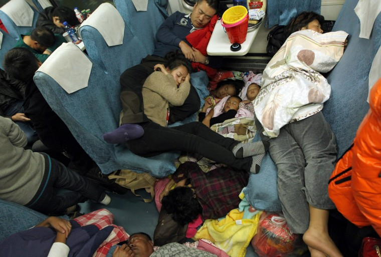 People sleep on their seats on the train from Guangzhou to Changchun to go back home for the Lunar New Year, or Spring Festival. Passengers will log 220 million train rides during the 40-day travel season as they criss-cross the country to celebrate with their families, but just as making the trip home can be laborious -- often lasting one or two days -- so can simply acquiring a seat on the train, and every year complaints arise about the inefficiency or unfairness of the system, although an initiative allowing travelers to purchase tickets online aims to curb long queuing times. (Getty Images)