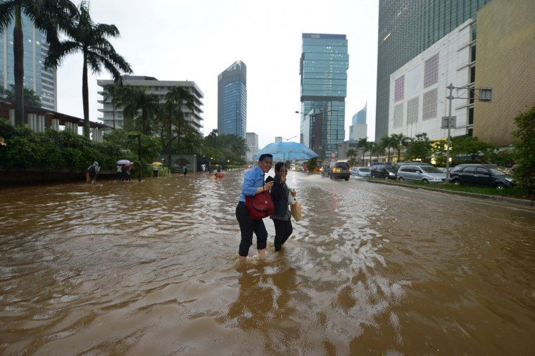 Indonesian people wade through a flooded main street in Jakarta. Heavy downpour caused floods on the streets even though Indonesian authorities used generators and cloud-seeding measures to defuse and push away rain-laden clouds. The rainy season is expected to last until March. (Adek Berry/Getty Images)