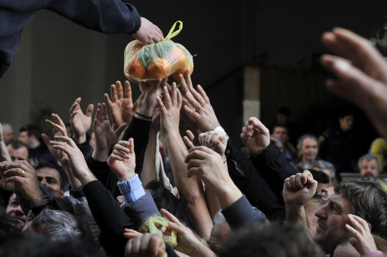 People reach out reach out for a bag of oranges during a free distribution of fruit and vegetables by Greek farmers outside the Agriculture Ministry in Athens part a farmers protest against high production costs, including petrol. Farmers distributed more than 50 tons of fruit and vegetables. (Louisa Gouliamaki/Getty Images)