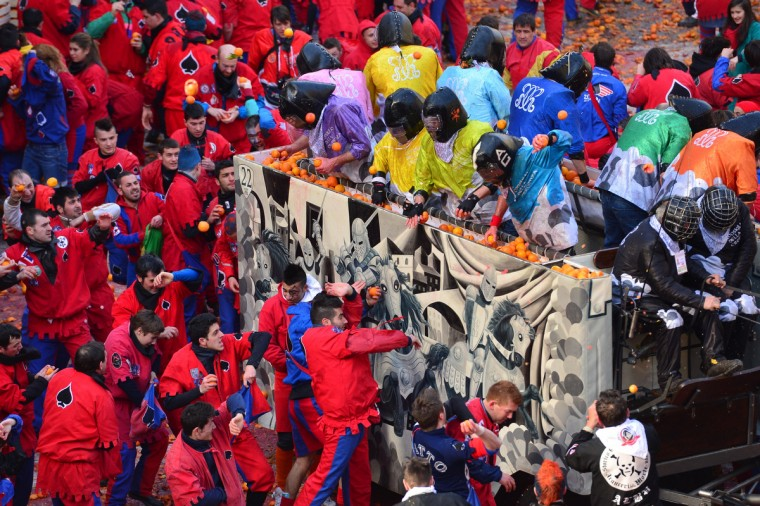 "Teams throw oranges at each other during the traditional ""battle of the oranges"" held during the carnival in Ivrea, near Turin, on February 10, 2013. During the event which marks the people's rebellion against tyrannical lords who ruled the town in the Middle Ages, revellers parading on floats represent guards of the tyrant, while those on foot the townsfolk. (Giuseppe Cacace/Getty Images)"