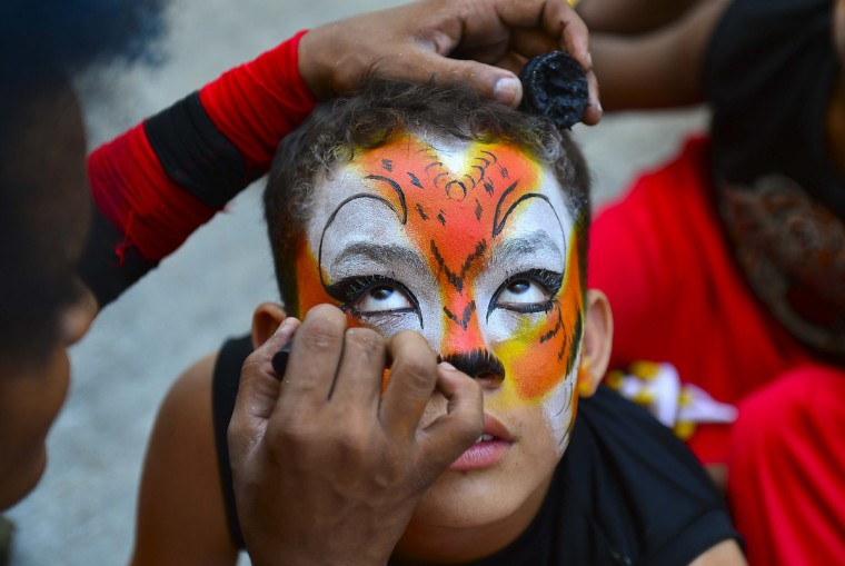"A man puts make-up on a child during the second day of carnival parade in Barranquilla, Colombia on February 10, 2013. Barranquilla's Carnival, a tradition created by locals at the end of the 19th century as a response and to parody the celebration held by European immigrants and aristocracy, was declared a ""Masterpiece of Oral and Intangible Heritage of Humanity"" by the UNESCO in 2003. (Luis Acosta/Getty Images)"