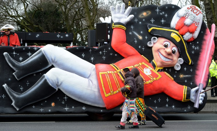 People pass carnival floats in the streets of Duesseldorf during the traditional Rose Monday parade on February 11, 2013. (Patrik Stollarz/Getty Images)