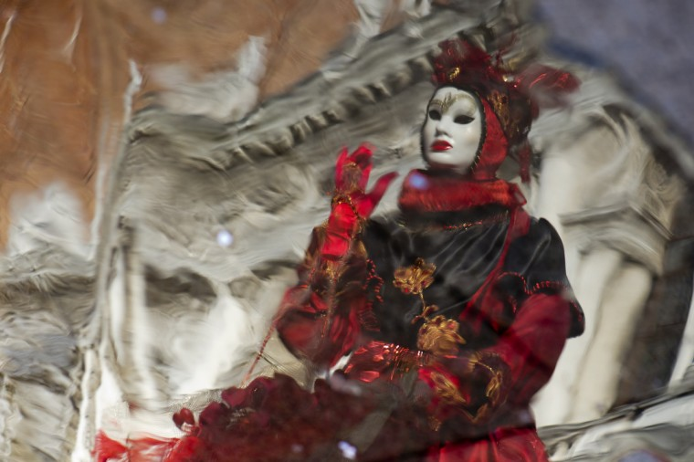 "A costumed reveller is reflected as water rises on St Mark's square during the carnival on February 8, 2013 in Venice. The 2013 edition of the Venice carnival is untitled "" Live in Colour"" and runs from January 26 to February 12. (Francois Xavier Marit/Getty Images)"