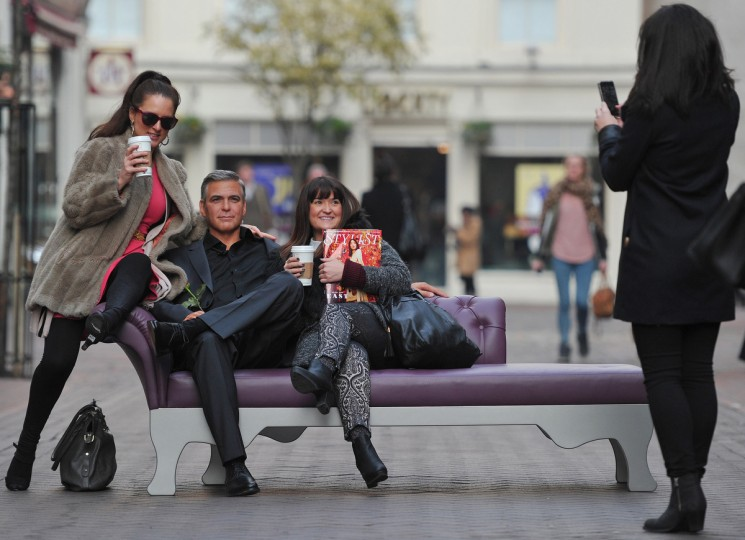 Members of the public pose for pictures with a waxwork model of US actor George Clooney during a photocall by London's Madame Tussauds to mark Valentines Day in central London. (Carl Court/Getty Images)