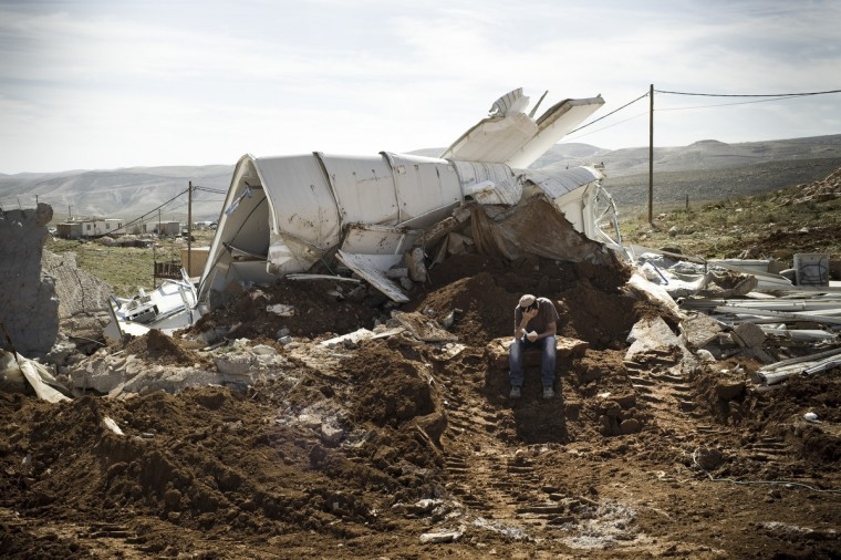 An Israeli settler sits praying among the rubble of his house that was demolished by Israeli police in the outpost of Maale Rehavam, in the Israeli occupied Palestinian West Bank. The house was built without any authorization outside the larger state-sanctioned settlement. The number of Israeli settlers in the occupied West Bank grew by 4.7% in 2012, according to figures obtained by AFP from a settler organization. (Janos Chiala/Getty Images)