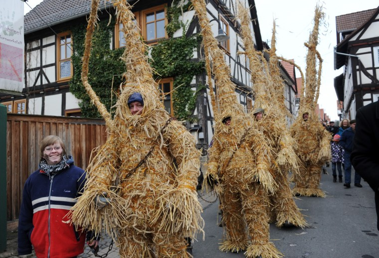 People dressed as straw bears walk through the streets in Heldra, Germany. On Ash Wednesday, people from the village dress as straw bears to drive out the winter. (Uwe Zucchi/Getty Images)