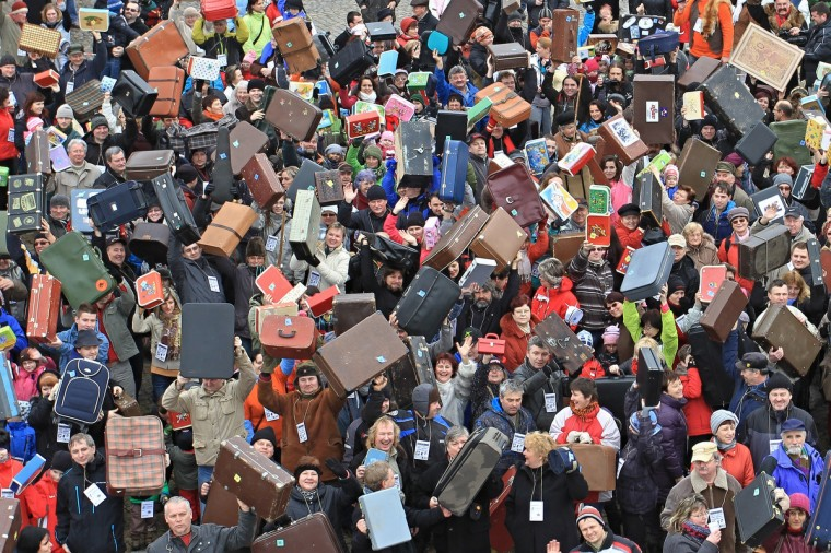 People holding up suitcases gather on Masaryk Square in Zabreh, central Moravia, Czech Republic, for an attempt to bring a record number of suitcases to one place. 579 people with suitcases came to the place to honor Czech adventurer, traveller and gold digger Jan Eskymo Welzl. The record will be officially registered in the Guinness Book of Records. (Radek Mica/Getty Images)