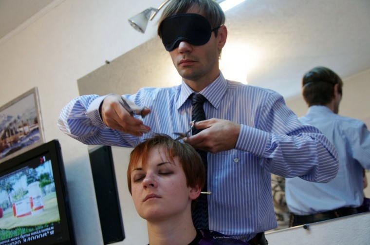 Oleg Maksyuk, a Ukrainian hair-stylist wearing a mask while using two pairs of scissors, cuts the hair of a client in a salon in the Ukrainian Black Sea city of Sevastopol. The hair-stylist mastered the unusual work style to attract more clients to his salon. (Vasiliy Batanov/Getty Images)