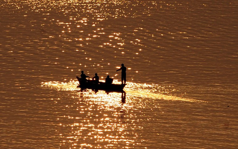 Indian fishermen catch fish in the Yamuna river in Allahabad. (Sanjay Kanojia/Getty Images)