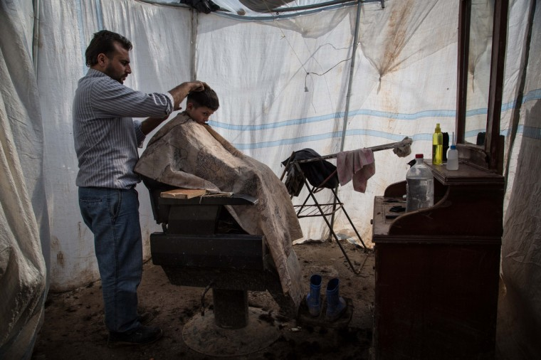 An internally displaced Syrian refugee child has a hair cut at a makeshift barber shop at the Azaz refugee camp along the Syrian-Turkish border. Some 15,000 refugees, mainly from the northern regions of Syria are living in this camp with no running water or electricity, in winter temperature that drop to under zero centigrade at night. (Chris Huby/Getty Images)