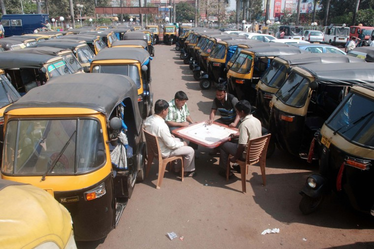"""Striking Indian auto-rickshaw drivers play carrom amid their vehicles at an auto stand during a two-day strike called by trade unions opposing the current UPA government's economic policies in Bhubaneswar. Millions of India's workers walked off their jobs on Wednesday in a two-day nationwide strike called by trade unions to protest at the """"anti-labour"""" policies of the embattled government. (Asit Kumarstrdel/Getty Images)"""