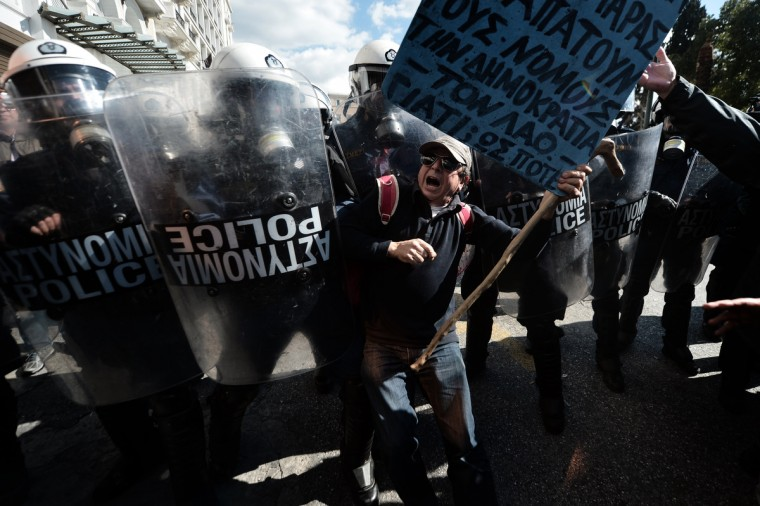 A demonstrator tries to pass a riot police cordon during a 24-hour general strike in Athens. Greece was hit by a new strike on February 20 called by leading unions against unrelenting austerity in the recession-weary nation ahead of an audit by international creditors, disrupting flights, ferries and hospital services. The strike -- the first general work stoppage in debt-crippled Greece this year -- has forced airport authorities to scrap or reschedule dozens of flights while hospitals were operating on reduced staffing. (Aris Messinis/Getty Images)