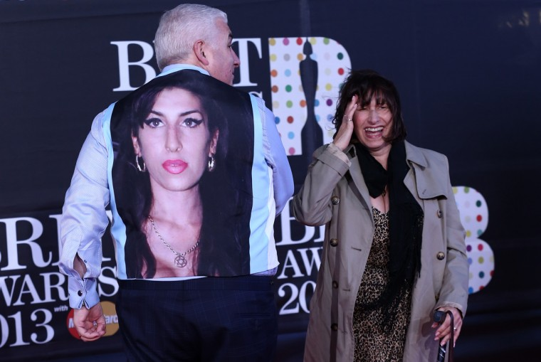 The parents of late British singer-songwriter Amy Winehouse (pictured on the back of Mitch), Mitch (L) and Janis (R) Winehouse, pose on the red carpet arriving at the BRIT Awards 2013 in London on February 20, 2013. (Andrew Cowie/Getty Images)