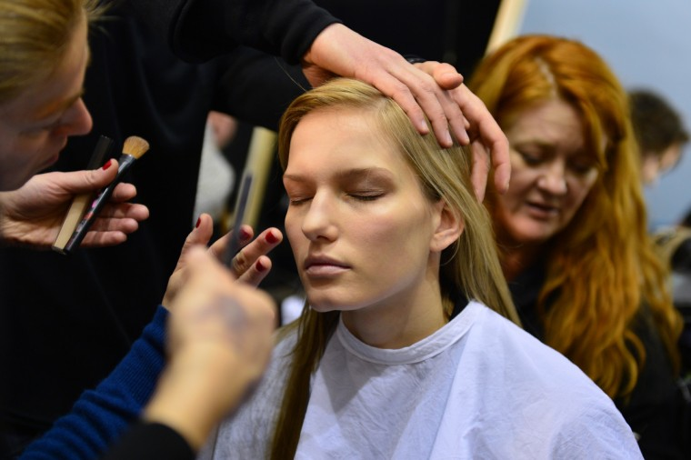 Hairdressers and make-up artists work on a model backstage prior the Trussardi Fall-Winter 2013-2014 Womenswear collection during the Women's fashion week in Milan. (Gabriel Bouys/Getty Images)