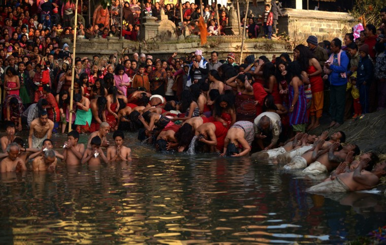 Nepalese Hindu devotees perform a bathing ritual on the last day of the month-long Swasthani Festival in the Hanumante River at Bhaktapur, on the outskirts of Kathmandu. Hundreds of married and unmarried women in the Himalayan nation are marking the last day of a month-long fast in the hope of a prosperous life and conjugal happiness. (Prakash Mathema/Getty Images)
