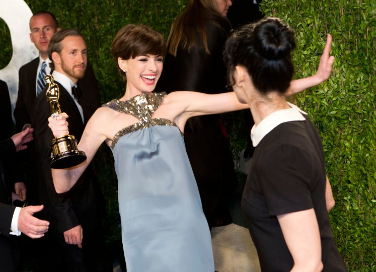 Anne Hathaway (L) carrying her Oscar for best supporting actress greets comedian Sarah Silverman as they arrive for the 2013 Vanity Fair Oscar Party on February 24, 2013 in Hollywood, California. (Adrian Sanchez-Gonzalez/Getty Images)