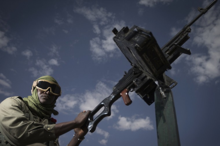 Malian army gunner Modibo Tangara, aged 22, stands beside a gun machine in Gao, some 1,200 kilometres (745 miles) north of Bamako. After recapturing the north's cities from the Al Qaeda groups that had controlled them since April 2012, the six-week-long French-led offensive took the fight to the retreating Islamist insurgents' toughest desert bastions. (Joel Sagat/Getty Images)