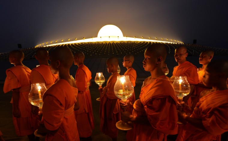 Buddhist monks hold candles as they walk around a Pagoda on Makha Bhucha Day at the Dhammakaya Temple in Pathumthani province. Makha Bhucha day is observed in Thailand on the full moon of the third lunar month and commemorates the day when 1,250 monks gathered to be ordained by the Buddha. (Pornchai Kittiwongsakul/Getty Images)