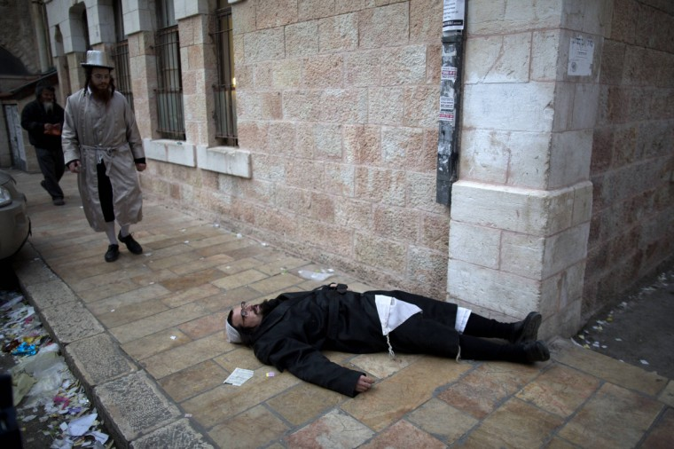 An Ultra-Orthodox Jewish man lies drunk on the sidewalk during celebrations for the Jewish festival of Purim in the religious neighborhood of Mea Shearim in Jerusalem. Purim marks the deliverance of the Jewish people from a genocidal plot in ancient Persia, as recorded in the Biblical Book of Esther. (Menahem Kahana/Getty Images)