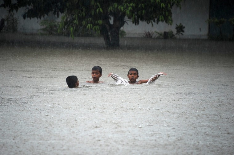 Boys play in flood waters in a school during heavy rain fall, as floods hit parts of Thailand's restive southern province of Narathiwat. Thailand's southernmost provinces near the Malaysian border suffer almost daily gun and bomb attacks by shadowy insurgents fighting for greater autonomy. (Madaree Tohlala/Getty Images)