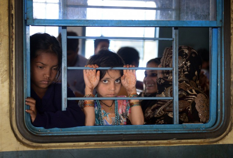 Indian passengers travel on a local train in New Delhi when Railway Minister Pawan Kumar Bansal unveiled the railway budget in parliament. The railway, the country's largest employer with some 1.4 million people on its payroll, runs 11,000 passenger and freight trains and carries 19 million people daily. (Raveendran/Getty Images)