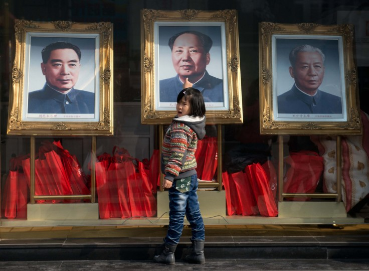 A girl stands before portraits of former Chinese leaders (L - R) Zhou Enlai, Mao Zedong and Liu Shaoqi in Beijing. On March 5 China will convene a key legislative session, state media reported, with new Communist Party chief Xi Jingping set to become president during the two-week meeting. (Ed Jones/Getty Images)