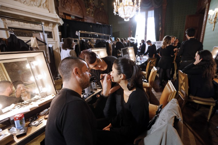 A man applies make-up on a model backstage prior to the start of Steffie Christiaens Fall/Winter 2013-2014 ready-to-wear collection fashion show in Paris. (Pierre Verdy/Getty Images)