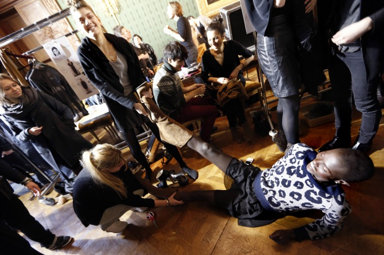 Models help a model to take off her boots backstage prior to the start of Steffie Christiaens Fall/Winter 2013-2014 ready-to-wear collection fashion show in Paris. (Pierre Verdy/Getty Images)