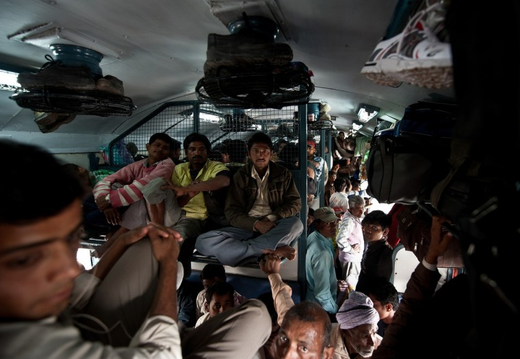 Indian women travel in a crowded coach on a train at a railway station in New Delhi when Railway Minister Pawan Kumar Bansal unveiled the railway budget in parliament. The railway, the country's largest employer with some 1.4 million people on its payroll, runs 11,000 passenger and freight trains and carries 19 million people daily. (Manan Vatsyayana/Getty Images)