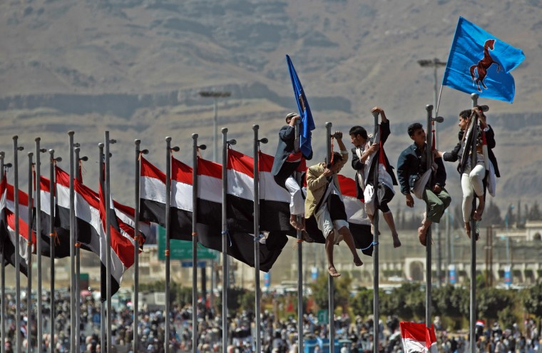 Supporters of former Yemeni president Ali Abdullah Saleh climb up flag poles flying their national flag during celebrations on the occasion of the first anniversary of the handover of power in Sanaa. Saleh stepped down after 33-years at the helm in February 2011 and formally handed power to his then deputy, Abdrabuh Mansur Hadi. (Mohammed Huwais/Getty Images)