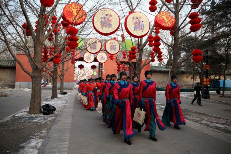 Chinese paramilitary police officers dressed as Qing Dynasty servants march before a re-enactment of an ancient ceremony of Qing Dynasty emperors praying for good harvest and fortune during the opening ceremony of the Spring Festival Temple Fair at the Temple of Earth park on February 9, 2013 in Beijing, China. The Chinese Lunar New Year of Snake also known as the Spring Festival, which is based on the Lunisolar Chinese calendar, is celebrated from the first day of the first month of the lunar year and ends with Lantern Festival on the Fifteenth day. (Feng Li/Getty Images)