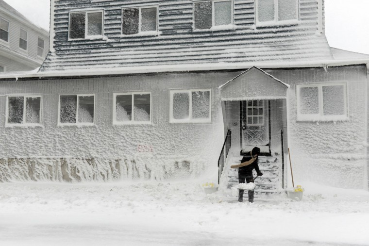 A man shovels snow along Winthrop Shore Drive in Winthrop, Mass., February 9, 2013. The storm has knocked out power to 650,000 and dumped more than two feet of snow in parts of New England. (Darren McCollester/Getty Images)