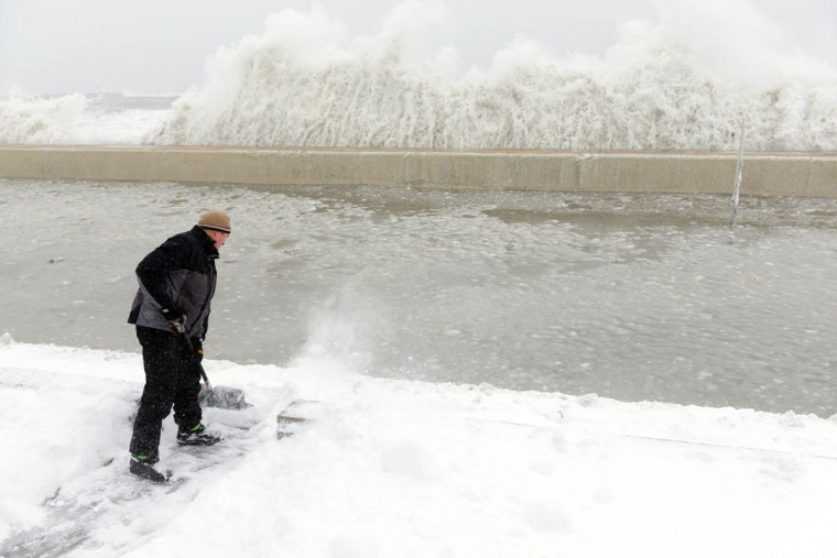 Mike Streeter shovels snow in his front yard as ocean water crashes over the sea wall just feet away on February 9, 2013 in Winthrop, Massachusetts. The powerful storm has knocked out power to 650,000 and dumped more than two feet of snow in parts of New England. (Darren McCollester/Getty Images)