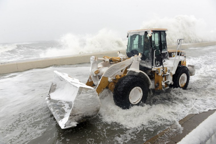 A snow plow goes down Winthrop Shore Drive as waves crash over the sea wall in Winthrop, Mass., on February 9, 2013. An overnight blizzard left one to two feet of snow in areas, and coastal flooding is expected as the storm lingers into the day. (Darren McCollester/Getty Images)