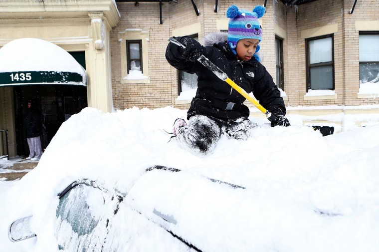 Saniyyah Phillips, 8, scrapes the snow off of the top of her father's car on February 9, 2013 in the Brighton neighborhood of Boston, Massachusetts. The powerful storm has knocked out power to 650,000 and dumped more than two feet of snow in parts of New England. (Jared Wickerham/Getty Images)