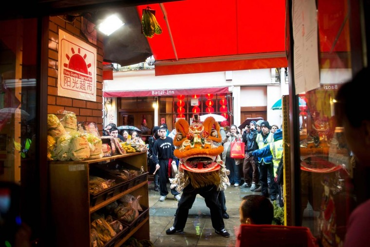 A lion dances in front of cabbage hanging in a shop doorway, a sign of prosperity for the coming new year on February 10, 2013 in London, England. London's Chinese community celebrate the start of the Year of The Snake with traditional dancing, music and fireworks. (Bethany Clarke/Getty Images)