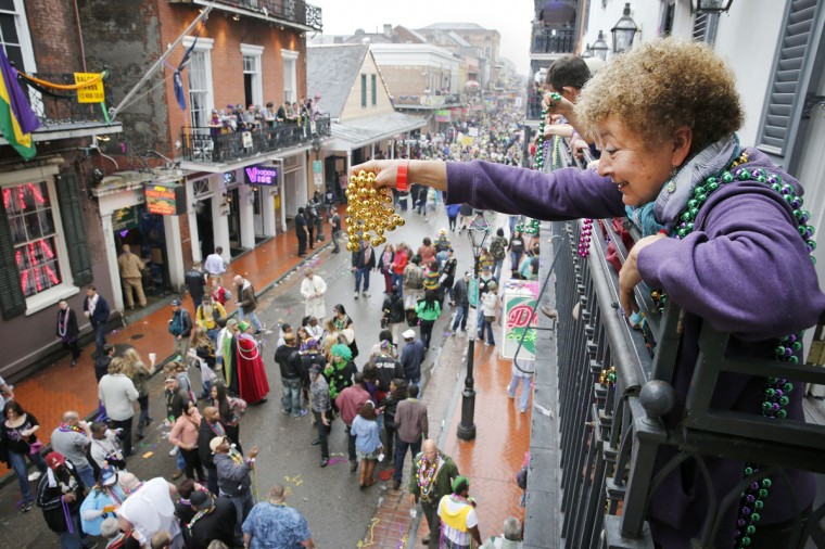 A Mardi Gras reveler dangles a pair of beads off of a balcony on Bourbon Street in New Orleans on Mardi Gras Day. (Rusty Costanza/Getty Images)
