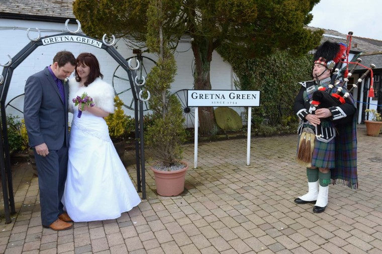 Jamie Blood and Bridget Foster pose on their wedding day at the Gretna Green Famous Blacksmiths Shop as a piper plays the bagpipes on Valentine's day on February 14, 2013 in Gretna, Scotland. Gretna Green is one of the most popular wedding destinations in Scotland hosting thousands of weddings each year with a particular rise on St Valentine's Day. Gretna Green has been hosting marriages in the blacksmiths shop since 1754. (Jeff J Mitchell/Getty Images)