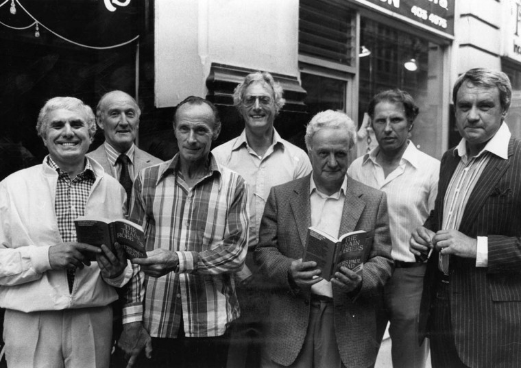 The Great Train Robbers, left to right: Buster Edwards, Tom Wisbey, Jim White, Bruce Reynolds, Roger Cordrey, Charlie Wilson and Jim Hussey, with copies of their book 'The Train Robbers'. (Michael Fresco/Getty Images)