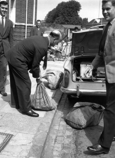 1963: Police officers put bags of evidence into a car boot after the Great Train Robbery. (Evening Standard/Getty Images)