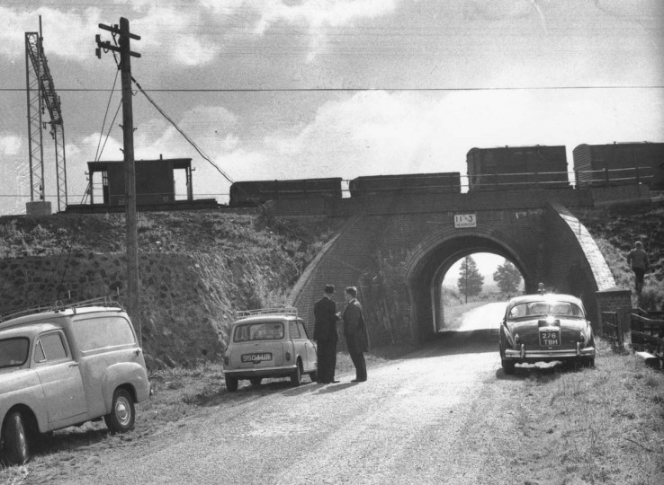 August 16, 1963: Investigators at the scene of the Great Train Robbery at Sears Crossing in Buckinghamshire, watching a train on the bridge. (Evening Standard/Getty Images)