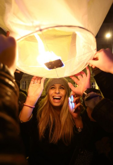 A girl smiles as Croatians gather in front of a museum in Zagreb to participate in an initiative by local artist Kresimir Tadija Kapulic (unseen) to release sky lanterns with people's Christmas and New Year's wishes, on December 20, 2012. (Stringer/AFP/Getty Images)