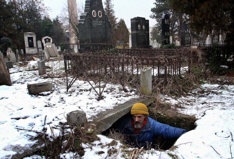 Bratislav Jovanovic enters a grave, which he uses as a shelter during winter time at a cemetery in Nis. Jovanovic has been homeless for nearly twenty years, since his house was burned down in a fire. The last 15 years he lives in a tomb beside the caskets of his decedents. Photo taken on January 10, 2013. (Sasa Djordjevic/AFP/Getty Images)