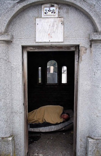 Aleksandar Dejic, 50, sleeps in a tomb he uses as a shelter during winter time at a cemetery in Nis. Dejic has been a homeless for twenty years and has no living family members. During winter with outside temperatures dropping below zero, he and his other homeless friends take shelter in the graves or above ground tombs at the old cemetery. Photo taken on January 10, 2013. (Sasa Djordjevic/AFP/Getty Images)