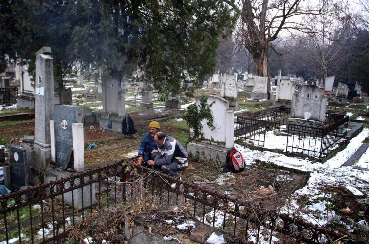 Bratislav Jovanovic and Aleksandar Dejic warm up beside a fire at a cemetery in Nis, 200 kilometres south of Belgrade. Photo taken Jan. 10, 2013. (Sasa Djordjevic/AFP/Getty Images)