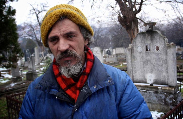 Bratislav Jovanovic stands beside a tomb at a cemetery in Nis. Jovanovic has been homeless for nearly twenty years, since his house was burned down in a fire. The last 15 years he lives in a tomb beside the caskets of his decedents. Photo taken Jan. 10, 2013. (Sasa Djordjevic/AFP/Getty Images)