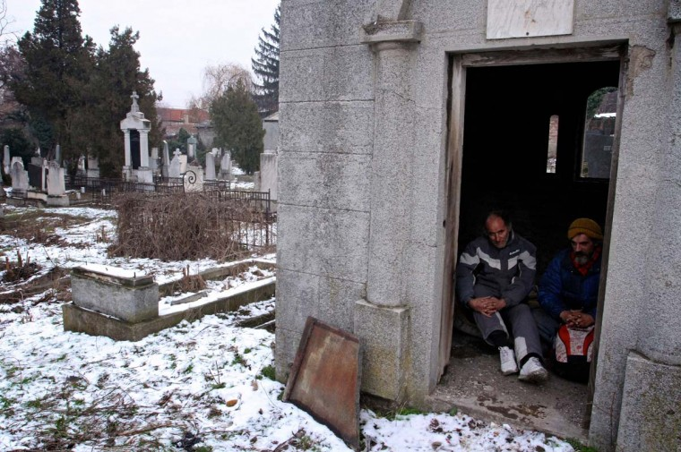 Bratislav Jovanovic and Aleksandar Dejic sit inside a tomb at a cemetery in Nis. During winter time with outside temperatures dropping below zero they take shelter in the graves or above ground tombs at the old cemetery. Photo taken Jan. 10, 2013. (Sasa Djordjevic/AFP/Getty Images)