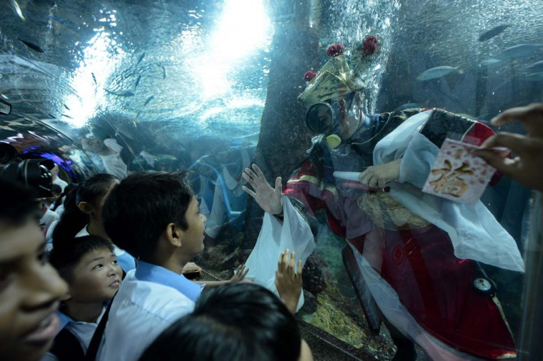 School children react to a diver (R) dressed as the God of Fortune in an aquarium at Underwater World Singapore on Sentosa's Island resort on February 5, 2013. The Chinese celebrate the Lunar New Year of the snake on February 10. (Roslan Rahman/AFP/Getty Images)